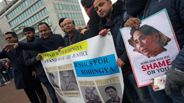Demonstrators hold signs outside the International Court of Justice in The Hague, where Myanmar leader Aung San Suu Kyi attended the first day of three days of hearings, Dec. 10, 2019. [AP]