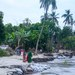 Villagers stand near a bank of the Padma River eroded by increased water flow in Bangladesh's Manikganj district, near Dhaka, Sept. 16, 2021.