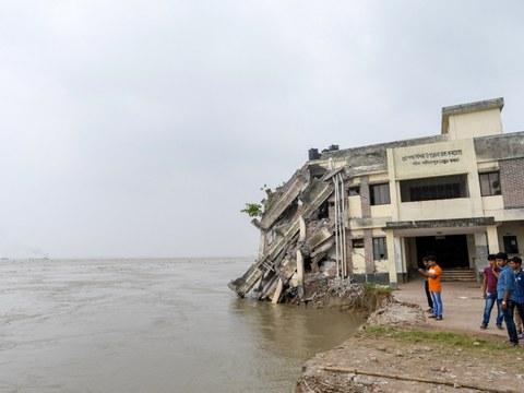 Bangladeshis gather next to a medical center building after soil erosion caused it to collapse into the Padma River about 40 km (25 miles) south of Dhaka, Sept. 13, 2018.
