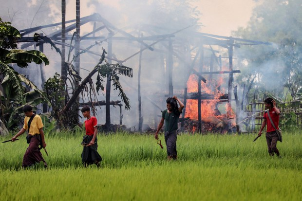 Unidentified men armed with knives and slingshots walk past the ruins of a burning house in Myanmar's Rakhine state where thousands of Rohingya fled following a military crackdown, Sept. 7, 2017.