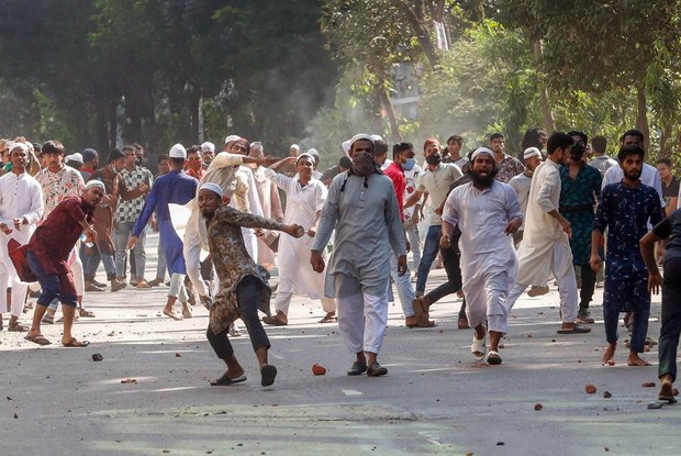 Muslim protesters throw stones as they clash with Bangladesh police in Dhaka over the alleged defamation of the Quran at a Hindu festival site, Oct. 15, 2021.