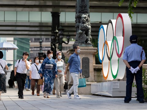 People walk past Olympics rings installed near the Nipponbashi Bridge in Tokyo, July 15, 2021.