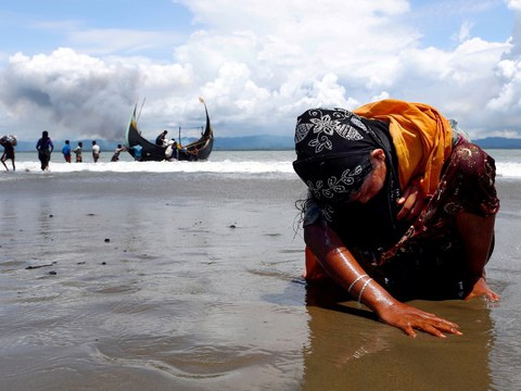 An exhausted Rohingya woman touches the shore after crossing the Bangladesh-Myanmar border by boat through the Bay of Bengal in Shah Porir Dwip, Bangladesh, Sept. 11, 2017.