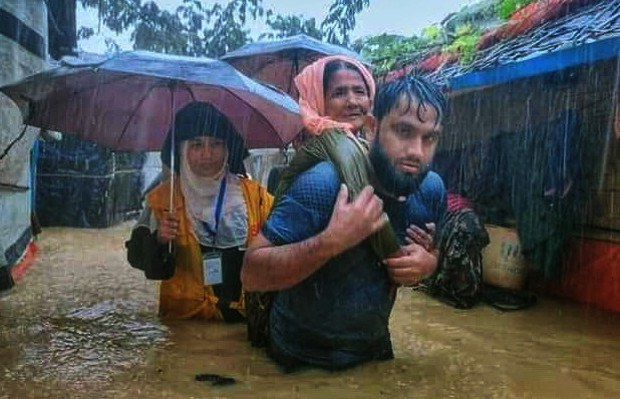 A Rohingya man carries a woman out of the flooded Balukhali refugee camp in Ukhia, a sub-district of Cox's Bazar, Bangladesh, July 27, 2021.