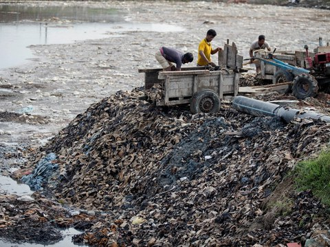 Bangladeshi workers unload tannery waste at the Tannery Industrial Area on the banks of the Dhaleshwari River in Savar, Bangladesh, June 28, 2018.