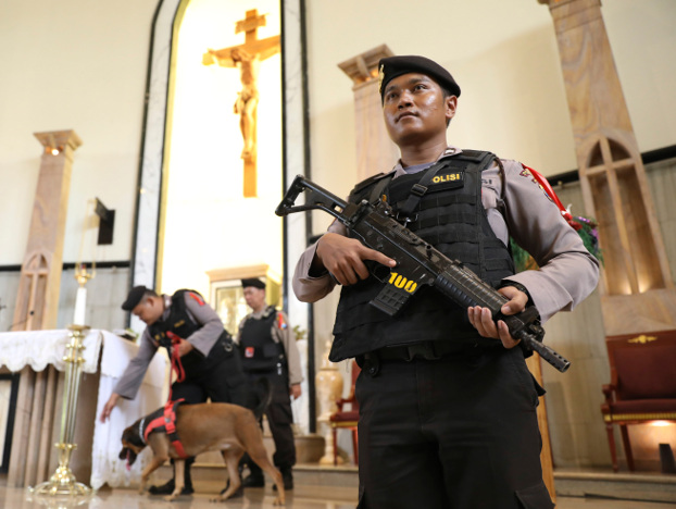 A police officer stands guard as the bomb squad lead a sniffer dog during a security sweep ahead of the Christmas holiday at The Good Shepherd Catholic Church in Surabaya, Indonesia, Monday, Dec. 23, 2019.