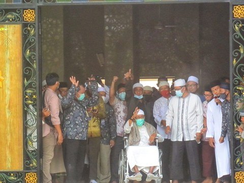 Cleric Abu Bakar Bashir waves from a wheelchair upon arriving at the Al Mukmin Islamic Boarding School where he resides near Solo, Indonesia, after his release from prison on terror-related charges, Jan. 8, 2021.