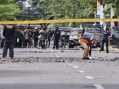Police officers inspect the area near a church where a bomb went off in a suspected suicide attack outside a Catholic church in Makassar, South Sulawesi, Indonesia, March 28, 2021.