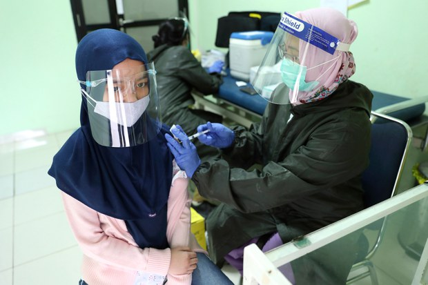 A student wearing a face mask as a precaution against the coronavirus outbreak receives a tetanus-diphtheria vaccine shot from a health worker in Jakarta, Oct. 27, 2020.
