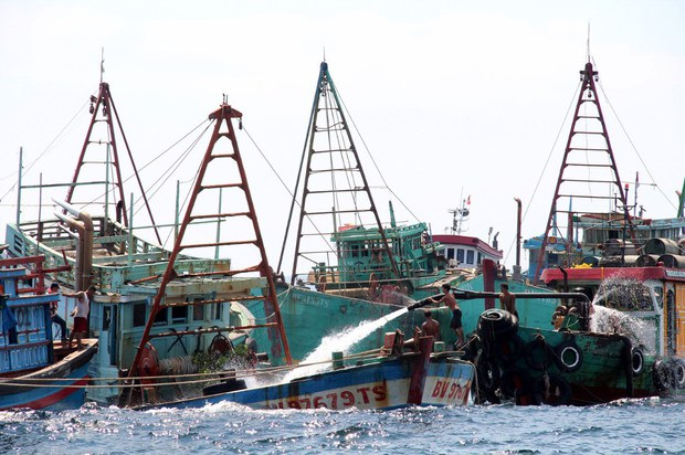 Workers fill Vietnamese fishing boats with water to sink them after they were seized over alleged illegal fishing in Indonesia's waters at Datuk island in West Kalimantan, May 4, 2019.
