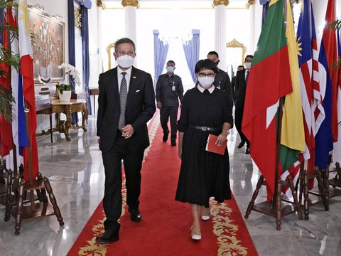 Indonesian Foreign Minister Retno Marsudi (right) and Singaporean counterpart Vivian Balakrishnan walk past flags of members of the Association of Southeast Asian Nations (ASEAN) during their meeting in Jakarta, March 25, 2021.