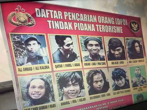 An old poster is seen of suspected Eastern Indonesia Mujahideen militants wanted by the authorities; Ali Kalora is pictured top left.