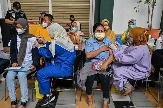 People receive a dose of the Chinese Sinovac COVID-19 vaccine at a mall in Surabaya, Indonesia, Sept. 23, 2021.