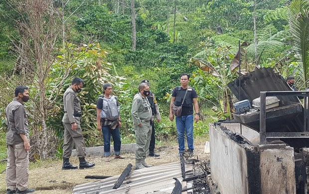 Central Sulawesi Police Chief Abdul Rakhman Baso (second right, front) stands in front of a home burned during an attack in Lembantongoa village blamed on the MIT terrorist group in which assailants killed four local residents, Nov. 28, 2020.