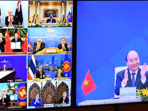 Vietnamese Prime Minister Nguyen Xuan Phuc (right) is pictured on a TV monitor clapping next to leaders of other nations who participated in a virtual signing ceremony for the Regional Comprehensive Economic Partnership trade pact, Nov. 15, 2020.