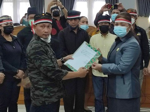 Sahir Sampeali (left), a representative of Lore Bersaudara district residents in Poso regency, presents an open letter to Indonesian President Joko Widodo to Poso Council Speaker Sesi K.D. Mapeda in Central Sulawesi, Indonesia, May 17, 2021.