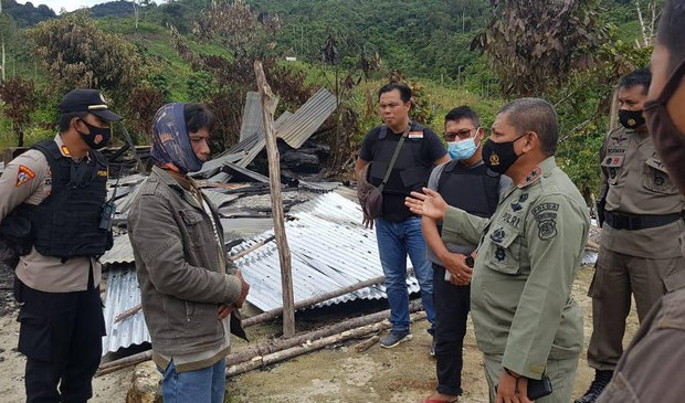 Abdul Rakhman Baso (right), the chief of police in Central Sulawesi province in Indonesia, talks with a resident at Lembantongoa village in Sigi regency, where suspected members of a pro-Islamic State militant group killed four local residents and torched homes, Nov. 28, 2020.