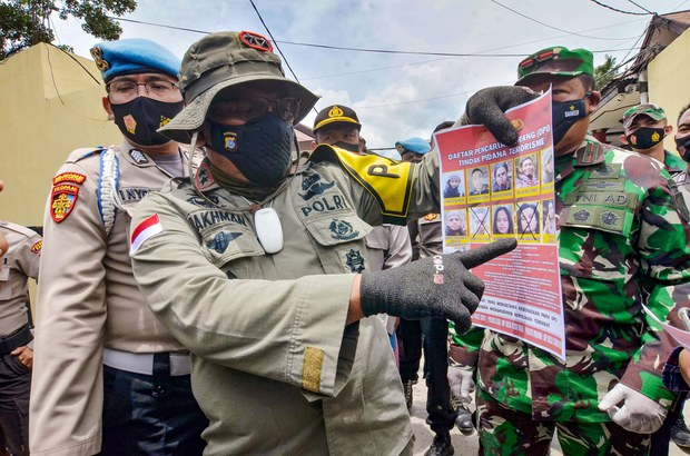 Inspector General Abdul Rakhman Baso, the police chief in Indonesia's Central Sulawesi province, shows a poster of wanted members of the Eastern Indonesia Mujahideen militant group, in Palu, March 2, 2021.