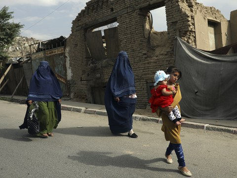 Afghan women in burqas and children walk on a street in Kabul, Afghanistan, Aug. 22, 2021.