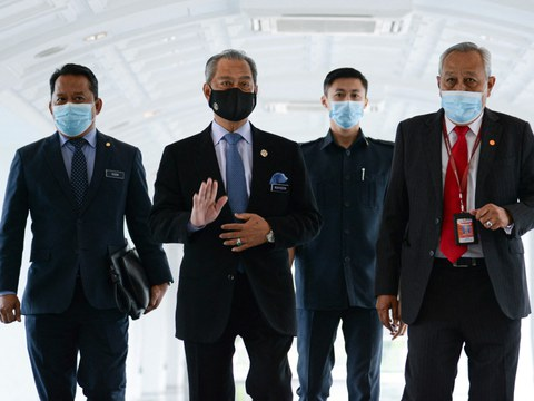 Malaysia's Prime Minister Muhyiddin Yassin (second from left) waves as he arrives for a session at the Malaysian Parliament in Kuala Lumpur, Nov. 26, 2020.