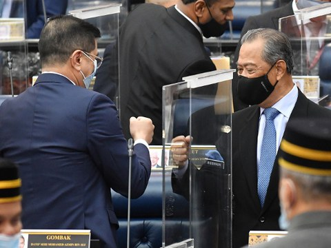 Malaysian Prime Minister Muhyiddin Yassin (right) bumps fists with Minister of International Trade and Industry Azmin Ali after his government's 2021 budget passed the first stage of a vote in Kuala Lumpur, Nov. 26, 2020.