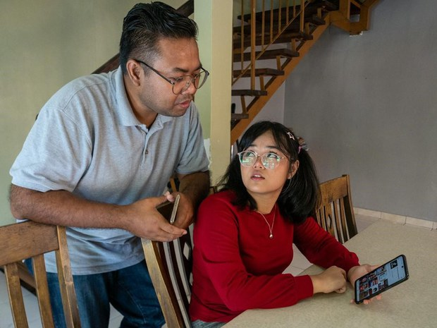 Seventeen-year-old Ain Husniza Saiful Nizam talks to her father about comments left on her TikTok video, in Kuala Selangor, Malaysia, May 8, 2021.