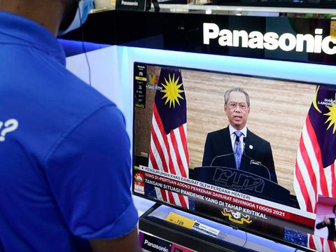 A worker at an electronics shop in Kuala Lumpur watches a live broadcast of Malaysian Prime Minister Muhyiddin Yassin addressing the nation, Jan. 12, 2021.