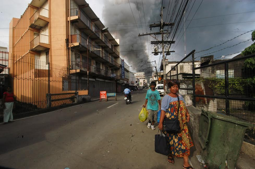 Smoke from fighting between government forces and MNLF rebels billows above downtown Zamboanga City, southern Philippines, in September 2013. [Froilan Gallardo/BenarNews]