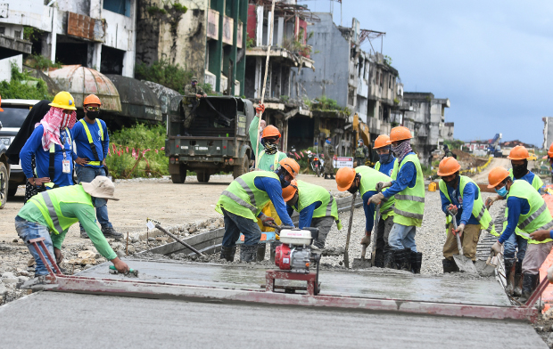 Workers pour cement along Quezon Avenue as part of efforts to rebuild streets and other infrastructure in war-torn Marawi, Oct. 17, 2020. [Froilan Gallardo/BenarNews]