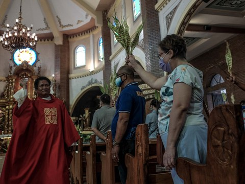 A priest blesses palm fronds as devotees attend Palm Sunday Mass at Santuario De San Juan Evangelista in Dagupan city, Philippines, April 1, 2020.