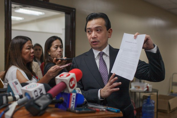 Then-Philippine Sen. Antonio Trillanes holds a copy of an amnesty order granted for his participation in military rebellions in 2003 and 2007 while speaking to reporters in Manila, Sept. 11, 2018.