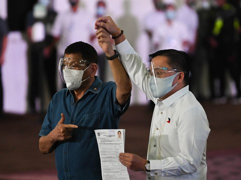 """Philippine President Rodrigo Duterte (left) accompanies Sen. Christopher """"Bong"""" Go as the lawmaker files his certificate of candidacy to enter the vice-presidential race, in Manila, Oct. 2, 2021."""