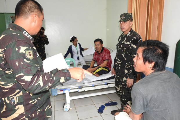 Philippine military officers interview Indonesian nationals Sarapuddin Koni (red shirt) and Sawal Maryam at a hospital in Jolo, southern Philippines, after they escaped from Abu Sayyaf militants who had kidnapped them, Sept. 7, 2017.