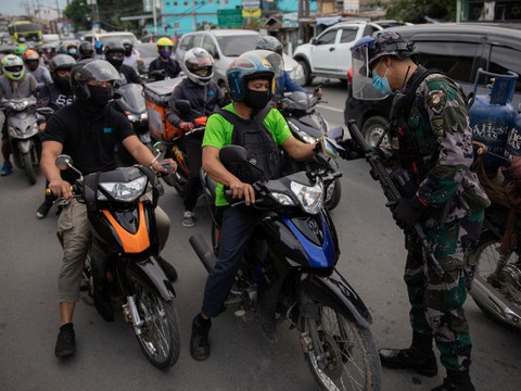 A police officer checks a motorist's ID at a checkpoint on the first day of the Philippine government's reimplementation of a stricter lockdown to curb coronavirus-disease infections, in Marikina City, Metro Manila, Aug. 4, 2020.