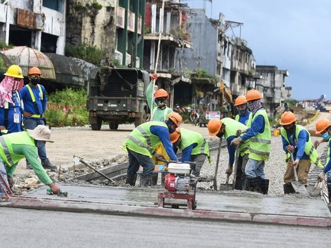 With soldiers providing security nearby, workers pour cement along Quezon Avenue in Marawi City, southern Philippines, Oct. 17, 2020.