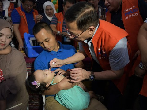 Health Secretary Francisco Duque III gives a dose of the oral polio vaccine (OPV) to a child in Marawi, southern Philippines, Oct. 14, 2019.