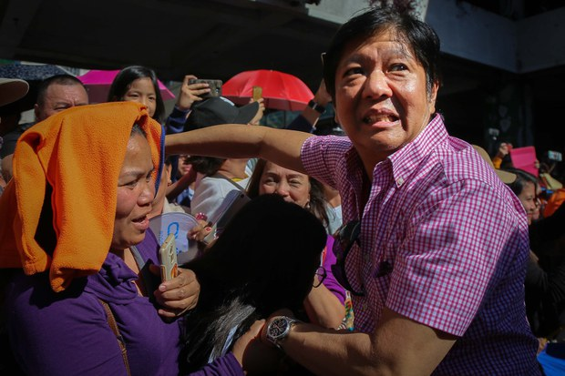 Former Philippine Sen. Ferdinand Marcos Jr. shakes hands with tourists during the Panagbenga Festival in the northern mountain resort city of Baguio, Feb. 24, 2018.
