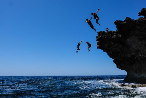 Tourists jump from a cliff at a beach in Bani municipality, Pangasinan province, Feb. 29, 2020.