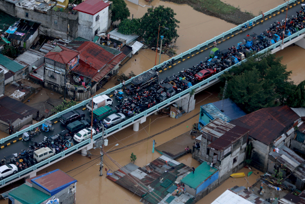 Vehicles and people stay on a bridge in Metro Manila to avoid floodwaters brought by Typhoon Vamco as others wait on rooftops to be rescued, Nov. 12, 2020. (Ace Morandante/Malacanang Presidential Photographers Division via AP)