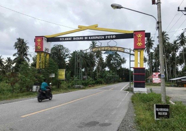 """A motorcyclist enters a gate that says """"Welcome to Poso Regency,"""" in Central Sulawesi, Indonesia, Nov. 21, 2020."""