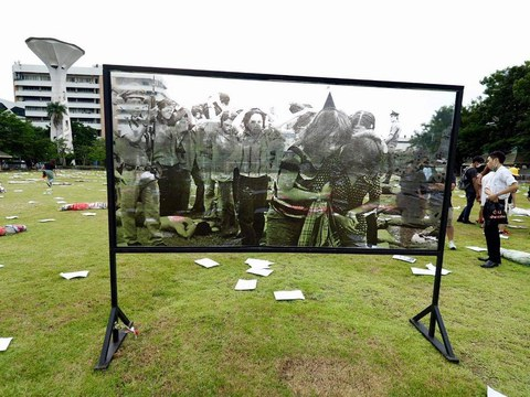An image on a screen shows a scene from an October 1976 massacre of student protesters by police at Thammasat University, as people at the Bangkok campus mark the 45th anniversary of the killings, Oct. 6, 2021.