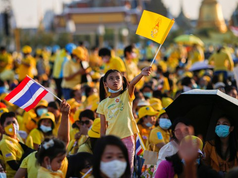 A child waves a flag ahead of a candlelight vigil to remember the birthday of Thailand's late King Bhumibol Adulyadej, outside the Grand Palace in Bangkok, Dec. 5, 2020.