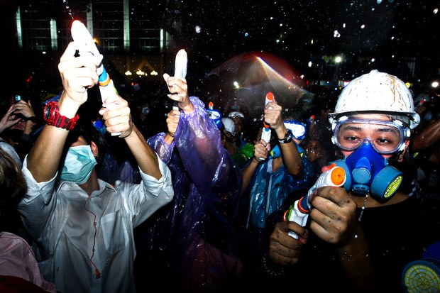 Pro-democracy demonstrators spray paint and water on the walls of the Royal Thai Police headquarters building in Bangkok, Nov. 18, 2020.