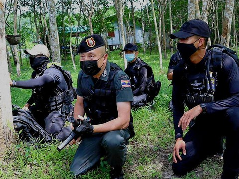 Police personnel search for suspected insurgents in Chamao Sam Ton village in Sai Buri, a district in Pattani province in Thailand, July 5, 2021.