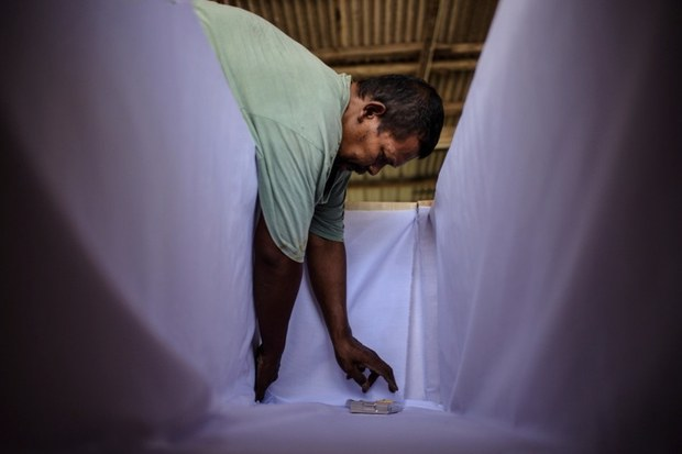Shahrul Kamaruzaman lines the inside of the coffin at his workshop in Port Klang, Malaysia, July 28, 2021.