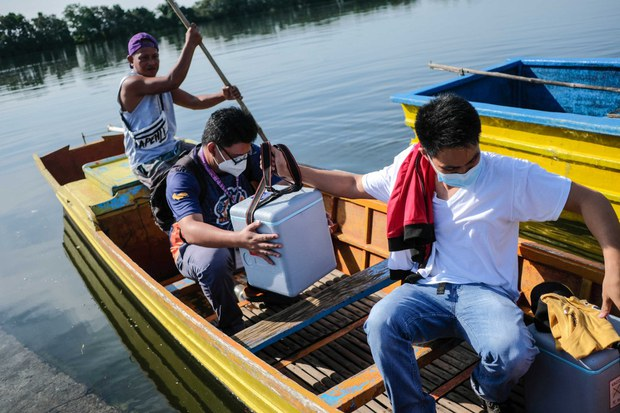 Health workers arrive by motorized canoe at a remote village in the town of Bani, Pangasinan province, where they set up a COVID-19 vaccination clinic, Sept. 7, 2021.